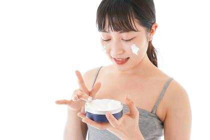 顔にクリームを塗る若い女性