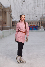 Young pretty woman dressed pink sweatshirt standing on ice in skates, outdoor ice-scating rink
