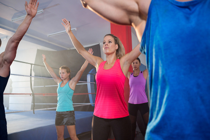 Athletes exercising with arms raised by boxing ring