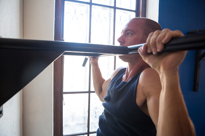 Male athlete practicing pull ups on bar by window