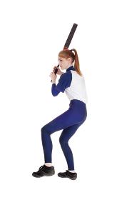 Woman swinging her bat in softball leg up