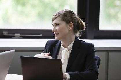 パソコンをしながら談笑するビジネスウーマン