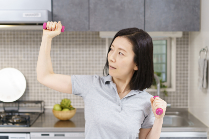 自宅の部屋で軽いダンベルをあげる運動をする中年女性
