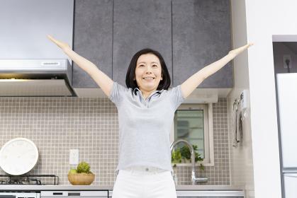 自宅の部屋で軽い運動をする中年女性