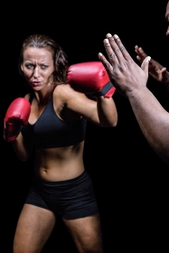 Female fighter hitting on trainer hand