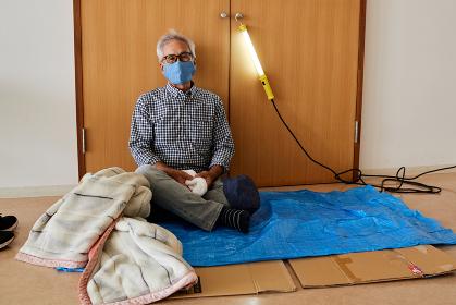 避難所イメージ 災害にあって避難所の体育館に避難してきたシニア男性
