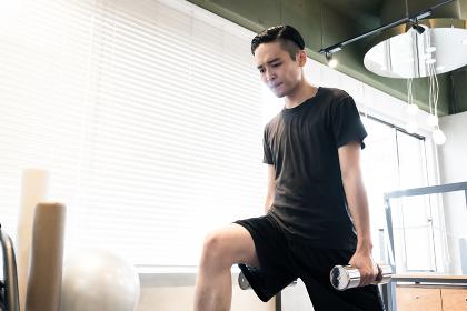 トレーニングジムで下半身を鍛える男性(ダンベルで重しをつける)