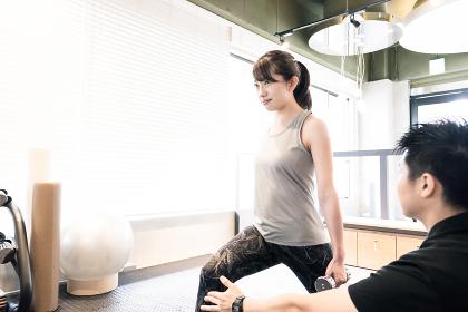 トレーニングジムで下半身を鍛える女性(ダンベルで重しをつける)