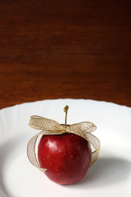 皿の上の金色のリボンで飾った姫リンゴ 2 縦位置