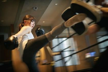 パーソナルトレーナーにキックボクシングを習うアジア人女性