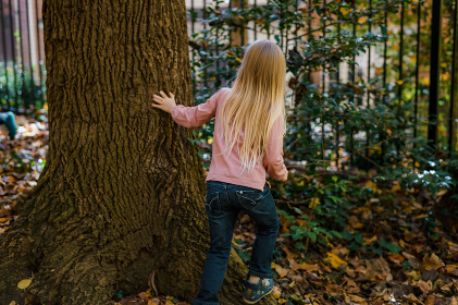 Little girl with long blonde hair looking behind tree